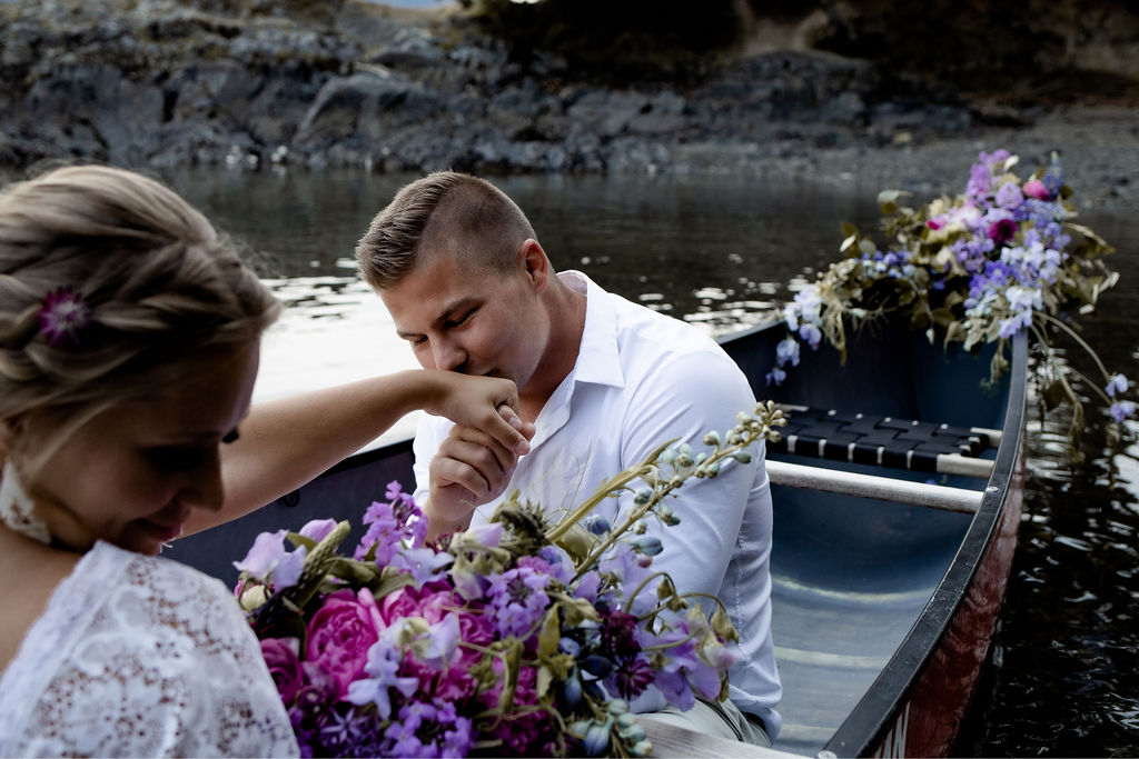 Groom kisses brides hand while sitting in a canoe on Vancouver Island
