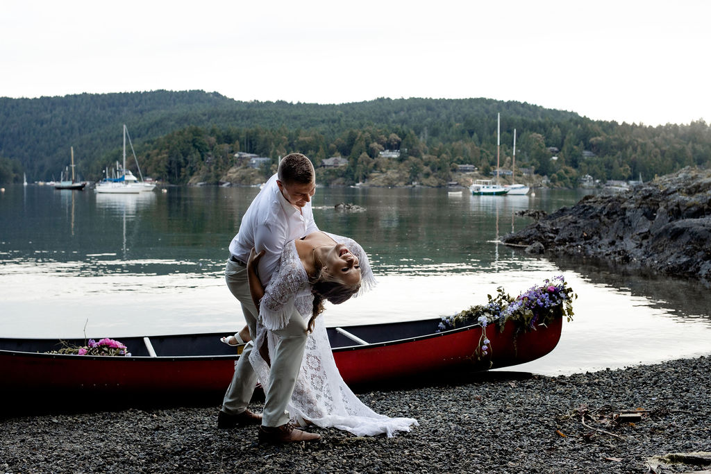 Groom dips his bride in front of a red canoe