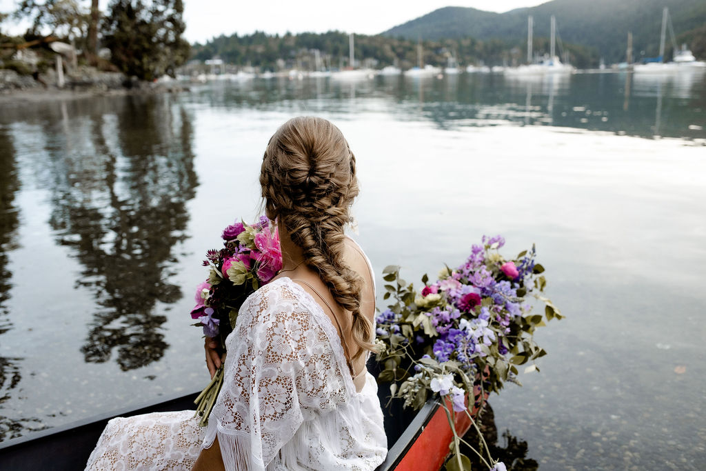 Bride with wedding day braid in her hair sits in canoe with flowers