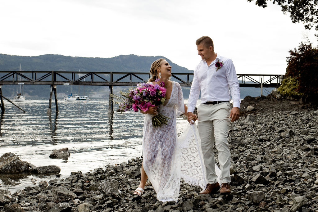 Newlyweds hold hands and walk along the stone beach on Vancouver Island