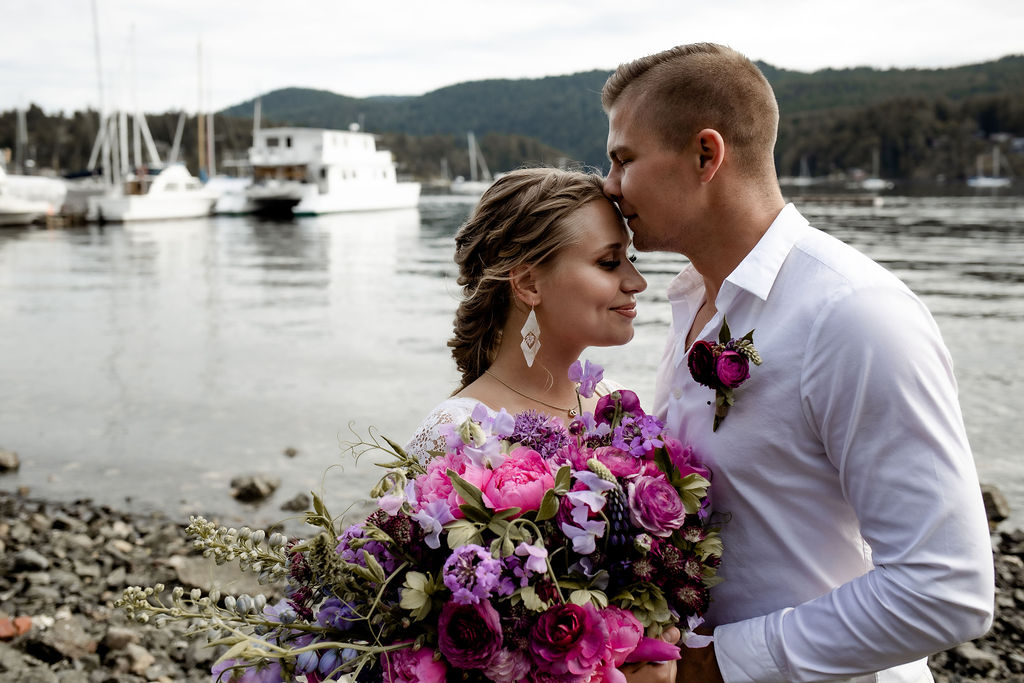 Newlyweds kiss with boat behind them on Vancouver Island