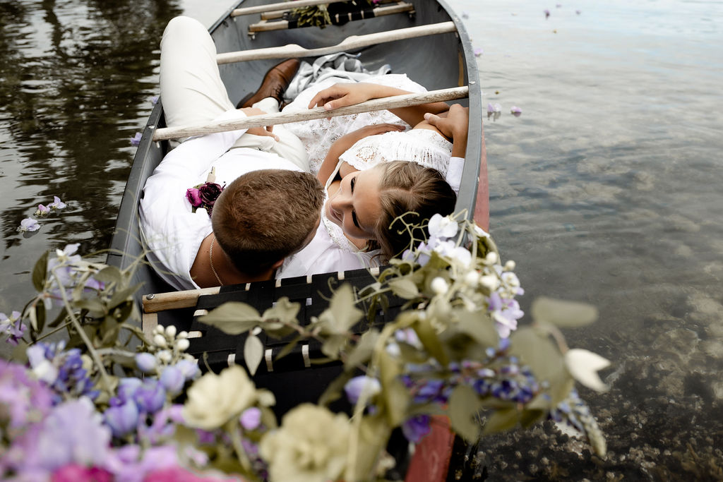 Adventure Elopement couple snuggle in the bottom of a canoe with flowers above them