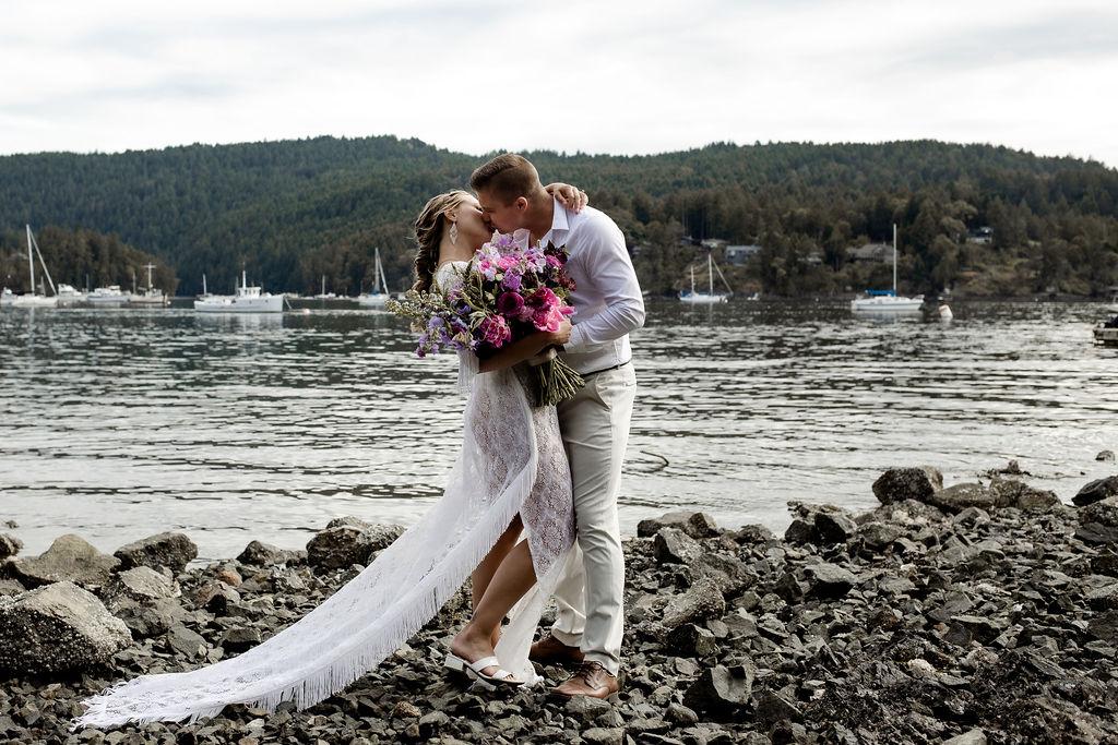 Newlyweds kiss along the ocean edge on Vancouver Island