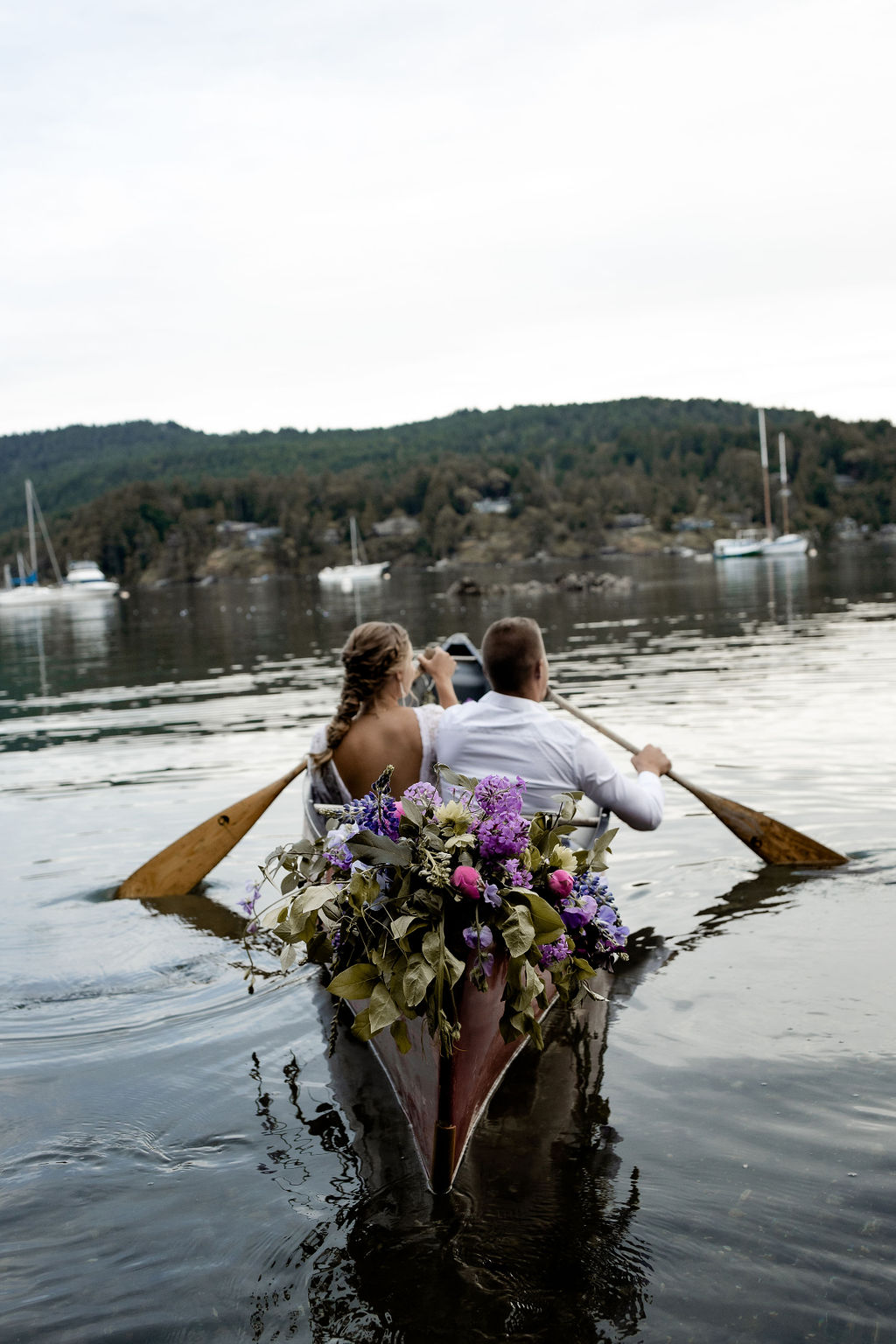 Newlyweds paddle canoe filled with purple and pink flowers on Vancouver Island